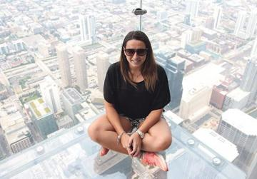 Chanel, the author, sitting on SkyLedge, a glass box extending outwards from the main structure of Willis Tower.