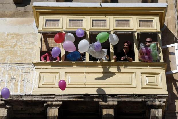 0576 Onlookers release balloons from their balcony as participants in the President's Solidarity Fun Run 2015 pass by their house in Floriana on November 15. Photo: Darrin Zammit Lupi