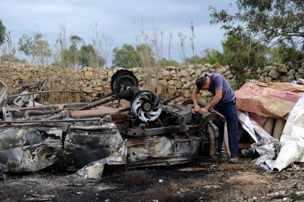 A fireworks enthusiast inspects the remains of car destroyed by a fireworks explosion a day earlier, in Gudja on October 31. Photo: Steve Zammit Lupi