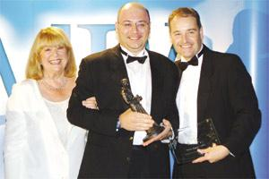 Melvin Bugeja (centre) with UK actress Nerys Hughes and Fuji`s UK marketing manager during the award ceremony