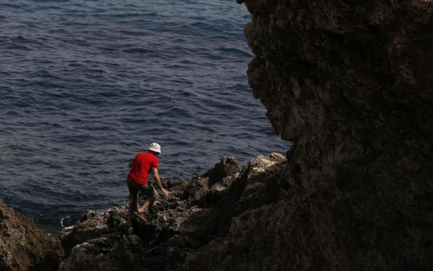 A man climbs on some rocks at Ghar Lapsi, outside Siggiewi, on April 13. Photo: Darrin Zammit Lupi