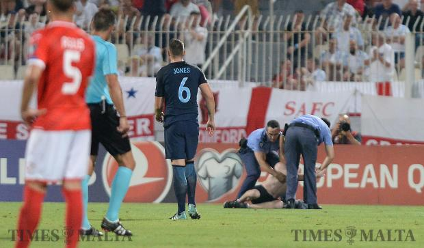 A fan it tackled by police after running onto the pitch during Malta's FIFA 2018 World cup Qualifying Group F Match against England at the National Stadium in Ta'Qali on September 1. Photo: Matthew Mirabelli