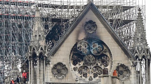 Inspectors are seen on the roof of the landmark Notre-Dame Cathedral yesterday, the day after a fire ripped through its main roof. Photo: AFP