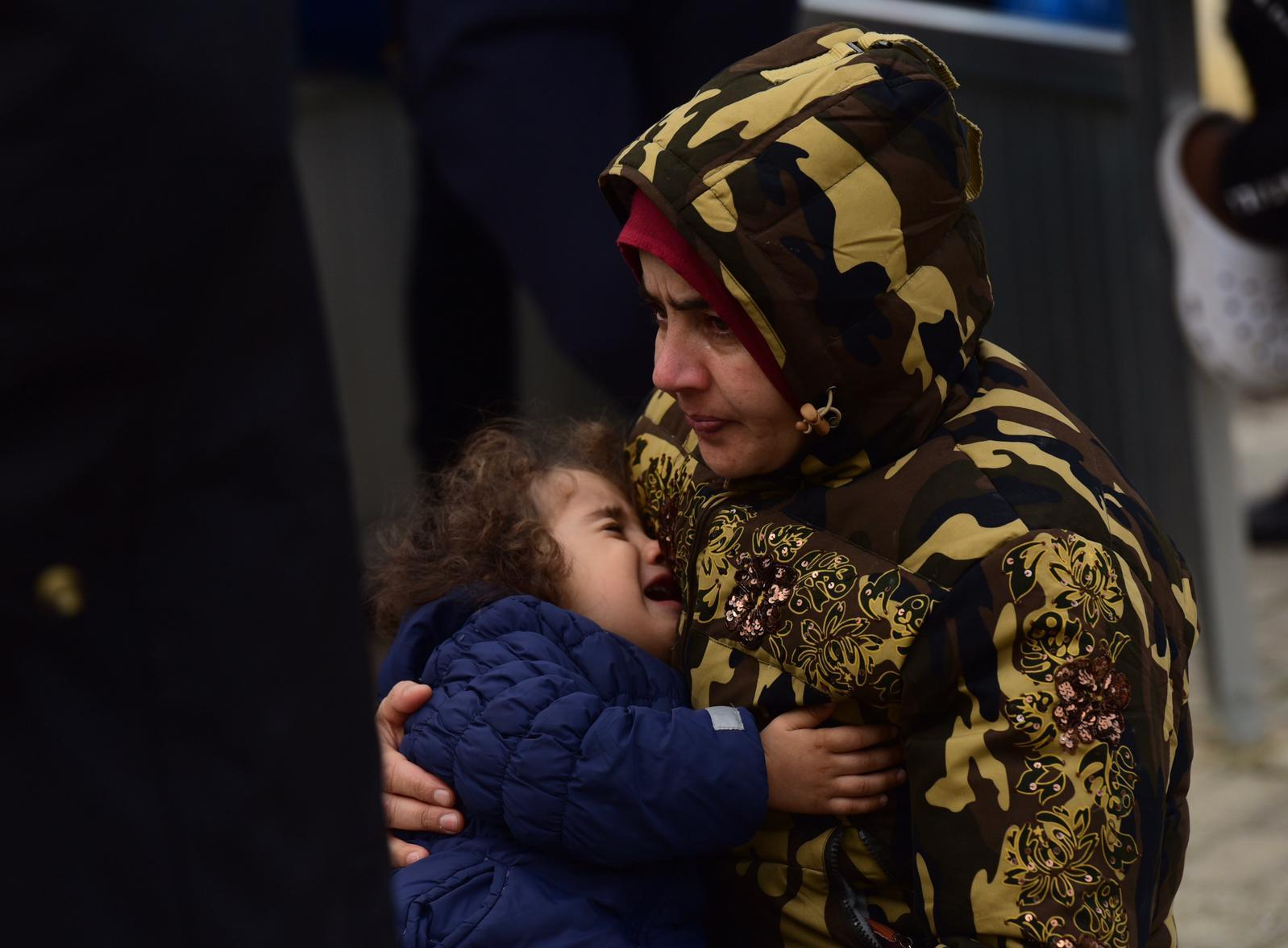 A tearful woman holds a crying child outside the Marsa centre following a fire on Wednesday January 8. Photo: Mark Zammit Cordina