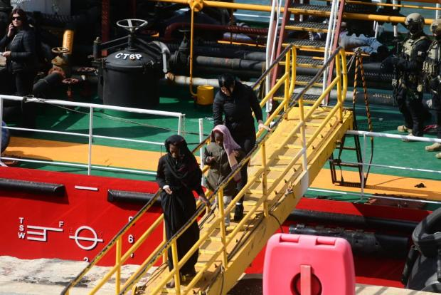 A migrant and her child disembark the vessel. Photo: Jonathan Borg