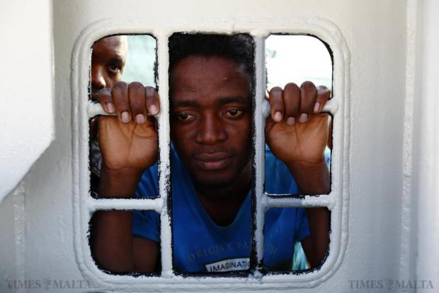 Migrants look out of a window on the Medecins san Frontiere (MSF) rescue ship Bourbon Argos as it arrives in Trapani, on the island of Sicily, on August 9. Some 241 mostly West African migrants on the ship were transferred to Italian authorities on arrival. Photo: Darrin Zammit Lupi