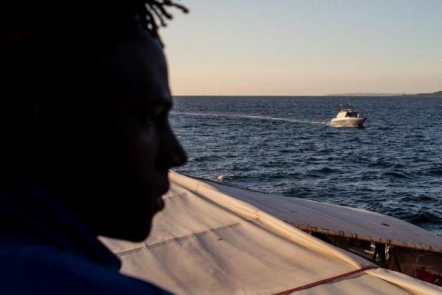 A migrant looks on from the deck of the Sea Watch 3 as it sails, escorted by a vessel of the Guardia di Finanza, off southeastern Sicily coats towards Catania.