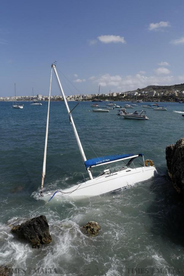 A sailing boat which cut its moorings in choppy waters caused by a north-easterly wind in St Paul's Bay crashes against the rocks at Fekruna Bay on August 23. No one was on board at the time. Photo: Darrin Zammit Lupi
