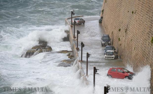 Waves churned up by strong north-easterly winds smash against parked cars in Valletta on October 28. Photo: Matthew Mirabelli