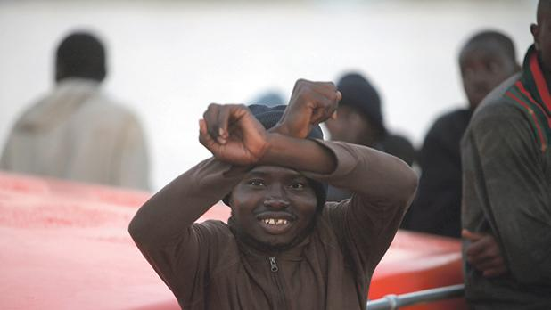 A migrant intercepted aboard a dinghy off the coast in the Mediterranean Sea, gestures on a rescue boat after arriving at the port of Malaga, southern Spain . PHOTO: Jon Nazca/REUTERS