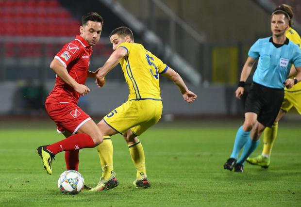 Andre Schembri (left) tries to move past Kosovo's Herolind Shala. Photo: Matthew Mirabelli