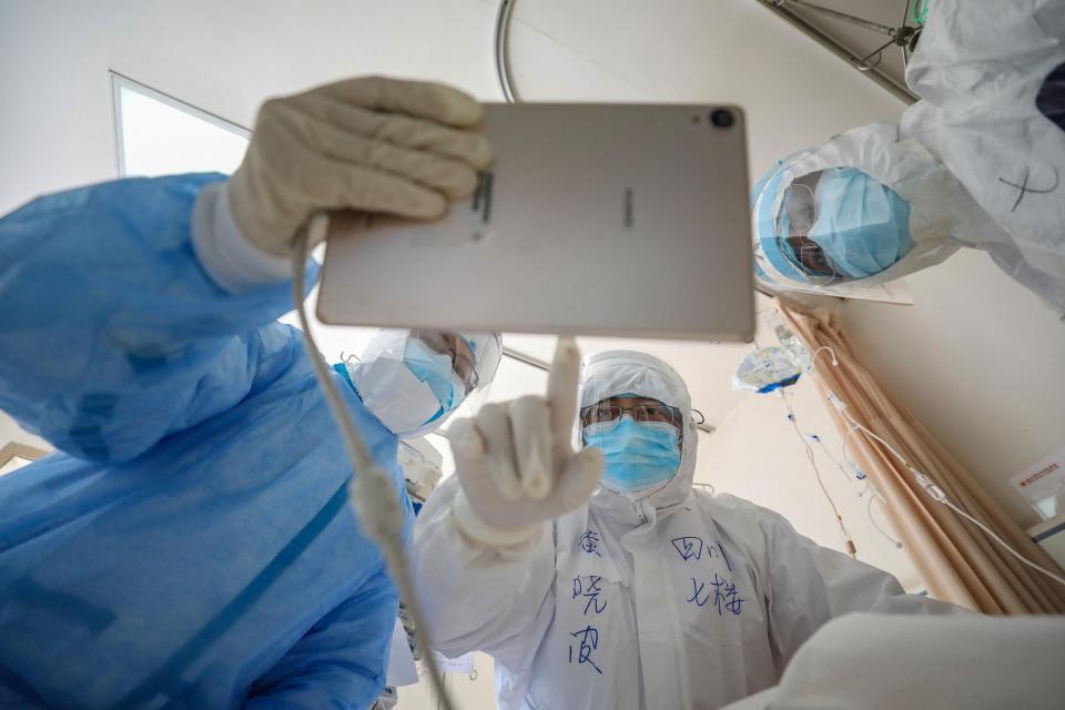 Esta foto de archivo tomada el 16 de febrero de 2020 muestra a un médico mirando una imagen mientras revisa a un paciente infectado por el coronavirus COVID-19 en el Hospital de la Cruz Roja de Wuhan en Wuhan en la provincia central de Hubei en China.
