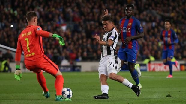 Juventus' Paulo Dybala in action with Barcelona's Marc-Andre ter Stegen.