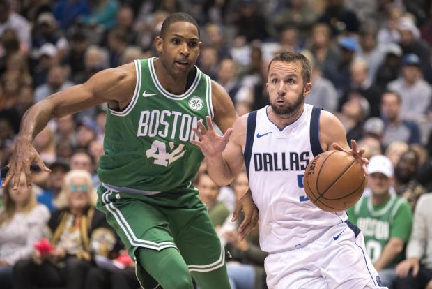 Dallas Maverics player J.J. Barea moves past Al Horford, of Boston Celtics.