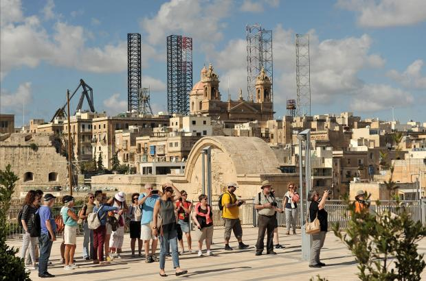The legs of 2 rigs pop up over the Senglea skyline on October 11. Photo: Chris Sant Fournier