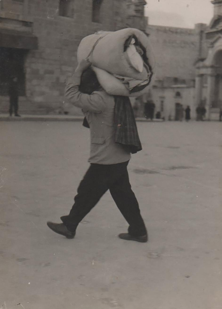 A refugee carrying his bedding as he leaves Valletta.