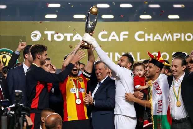 Esperance players celebrate winning the final with the trophy.