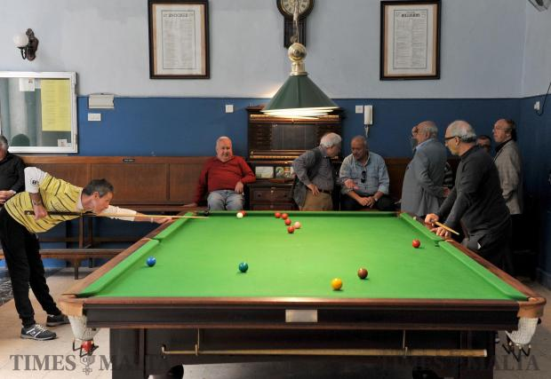 A snooker player takes aim while men chat at the La Vallette band club in Valletta on May 2. Photo: Chris Sant Fournier