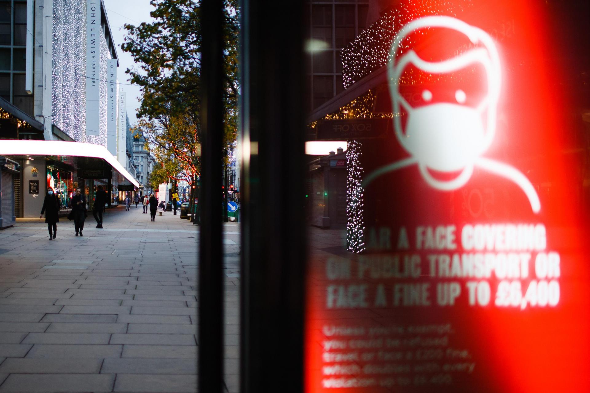 A sign reminding public transport users to wear face coverings lights up the digital advertising screen of a bus stop on a quiet Oxford Street in London, England.