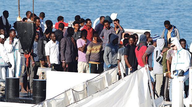 Migrants wait to disembark Italian Coast Guard's vessel Diciotti as they arrive at the Catania harbour, Italy. Photo: Antonio Parrinello/Reuters