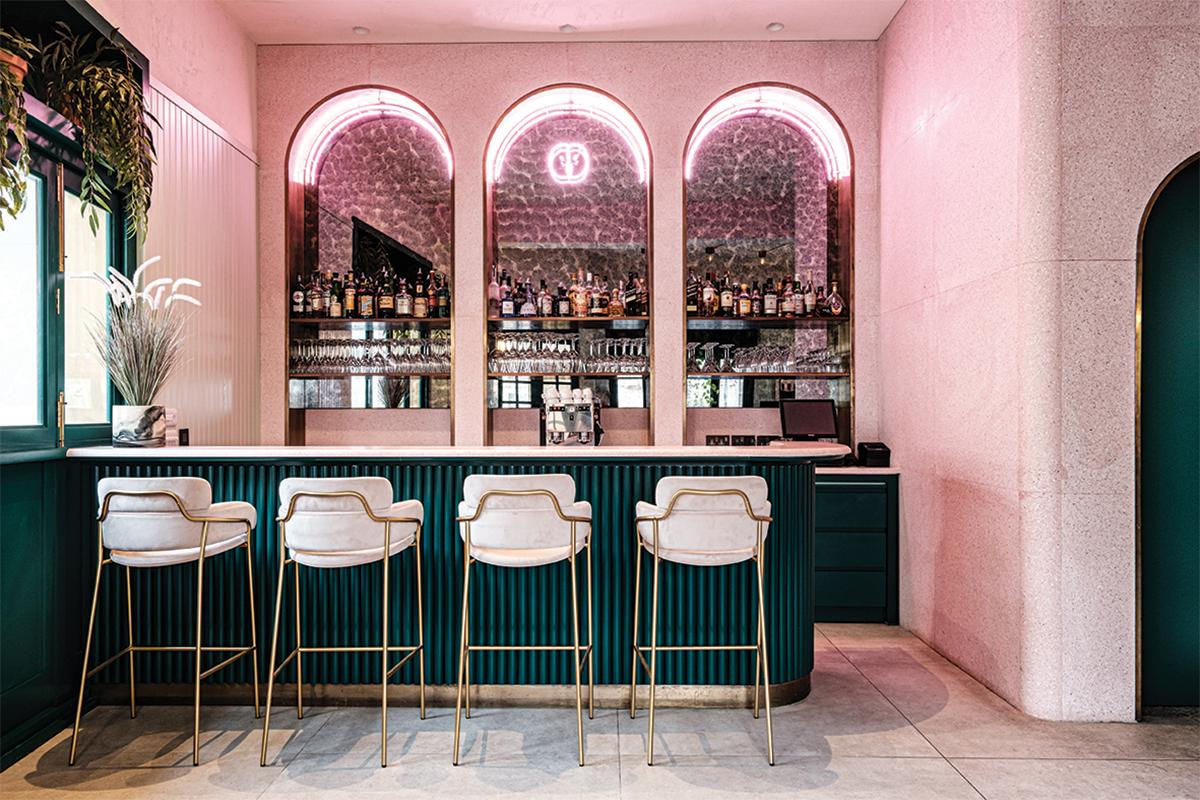 The bar is a focal point for the entire interior space, inspired by the elegance of European art deco bistros.