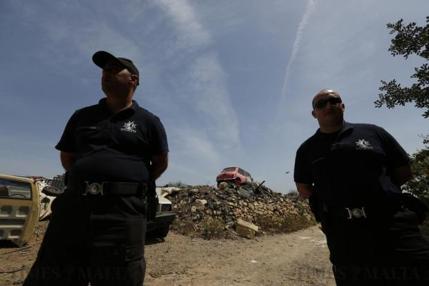 Police officers look on after being called to intervene when the owners of an illegal scrapyard at Ta' Harbat (between Zejtun and Birzebbuga) resisted efforts by planning authority officials to clear the area on April 19. Photo: Darrin Zammit Lupi