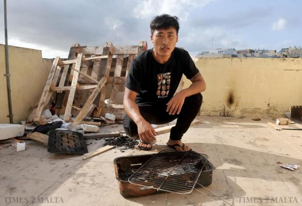Xiao Guan is forced to cook on the roof of his Marsa flat to avoid paying to use its kitchen on October 15. Photo: Chris Sant Fournier