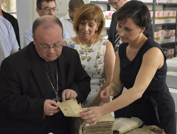 Archbishop Charles Scicluna is shown a document at the National Notarial Archives in Valletta on July 24. Photo: Mark Zammit Cordina