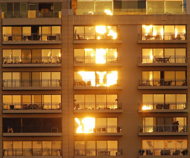 The setting sun is reflected off apartment balcony windows along the Sliema sea front on August 24. Photo: Darrin Zammit Lupi