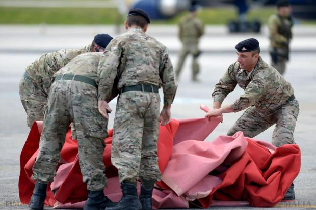 Members of the Armed Forces of Malta gather the red carpet shortly after the Queen and her husband Prince Philip boarded their plane bringing to an end their three-day state visit to Malta on November 28. Photo: Matthew Mirabelli