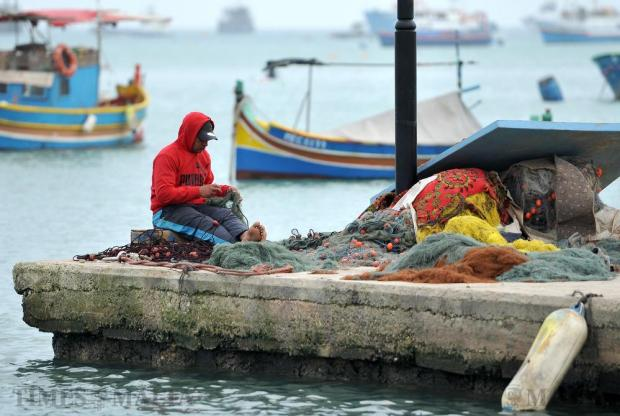 A man prepares his fishing nets on the quay in Marsaxlokk on February 17. Photo: Chris Sant Fournier