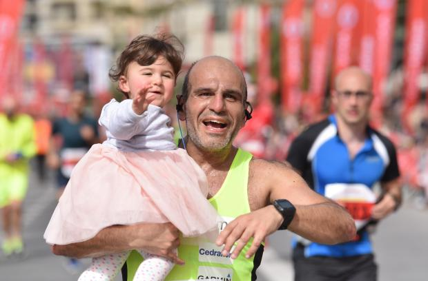 A man holds a young girl at the final stage of the Malta Marathon in Sliema on February 25. PHOTO: MARK ZAMMIT CORDINA