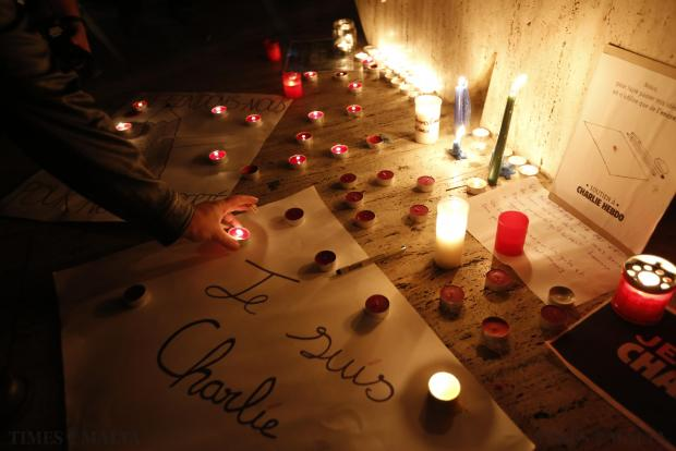 "People place placards reading ""I am Charlie"", cartoons and candles in front of the Love monument as a tribute to victims in St Julian's on January 8, following a shooting by gunmen at the offices of weekly satirical magazine Charlie Hebdo in Paris. Photo: Darrin Zammit Lupi"