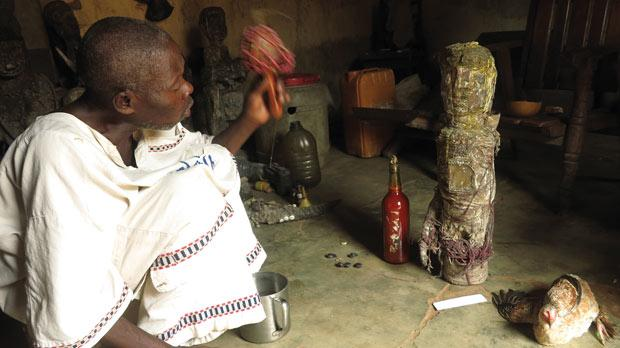 The voodoo doctor performing a ceremony in Abomey, with a deity, on right, covered in chicken blood and gin.