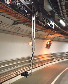 The robotic arm extending from a train inspection monorail, equipped with the camera used to capture images of the tunnel wall.