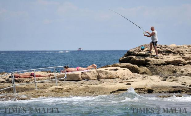 A man casts his fishing line from a Bugibba rock on August 24. Photo: Chris Sant Fournier
