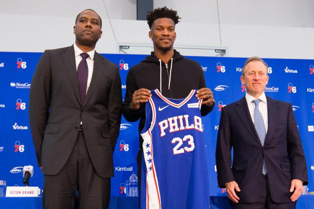 Philadelphia 76ers guard Jimmy Butler (23) holds his new uniform next to general manager Elton Brand (L) and managing partner Josh Harris (R) during a press conference at the Philadelphia 76ers Training Complex. Mandatory Credit: Bill Streicher-USA TODAY Sports