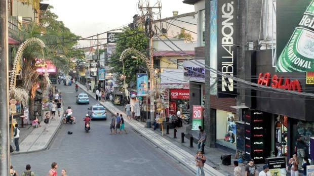 Legian Street in Kuta where high street shops meet bars and traffic.