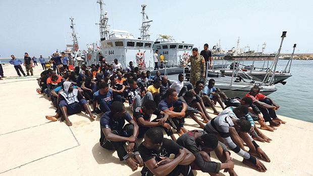 Migrants sit at a naval base after being rescued by Libyan coast guards in Tripoli, Libya. Photo: Ismail Zitouny/Reuters