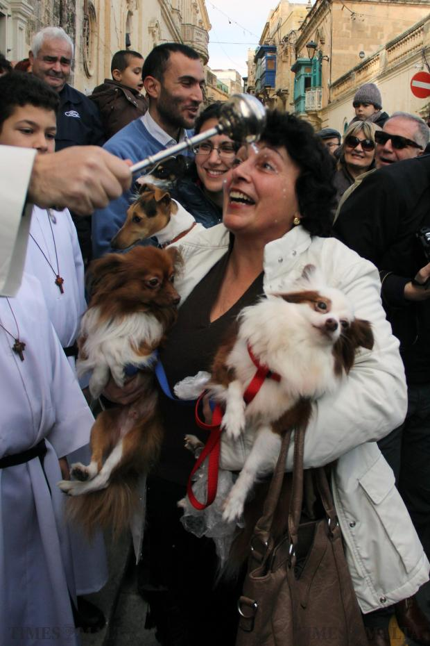A woman seems very happy that her two dogs are being blessed during the traditional animal blessings in Rabat on January 10. Photo: Paul Spiteri Lucas