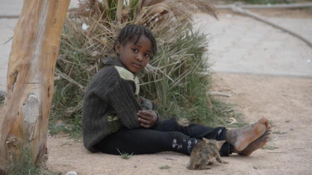 A little girl sits outdoors with a kitten on the grounds of the Misurata Detention Centre, a facility that can house up to 600 migrants. In an interview with three detainees at the centre, Migrant Report was told by the young men from Nigeria and Mali they were desperate to call home because they feared their families believed them dead. They were not given the opportunity to call home since being detained. Migrant Report helped them get in touch with their families while the guards were distracted. Photo: Robert Young Pelton, Migrant Report