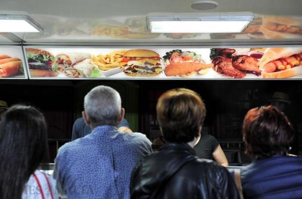 People queue up for junk food at a kiosk at the Valletta FC funeral on April 6. Photo: Chris Sant Fournier