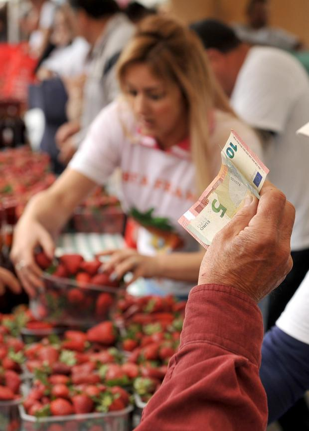 A woman waves Euro notes in an attempt to attract attention to buy strawberries at the annual Strawberry Festival in Mgarr on April 2. Photo: Chris Sant Fournier