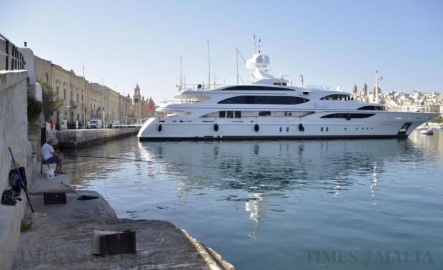 A man fishes next to the super yacht Lady Luck at Vittoriosa on July 4. Photo: Mark Zammit Cordina