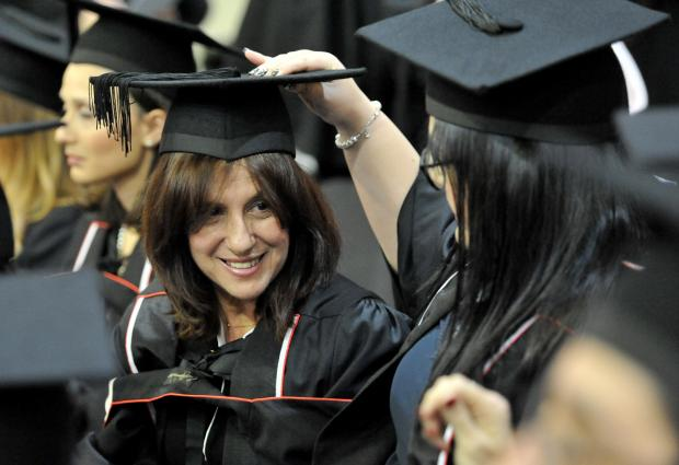 A graduate arranges the hat of another graduate at their graduation ceremony on December 6. Photo: Chris Sant Fournier