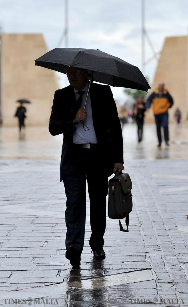 A man shelters under an umbrella in Valletta on May 18. Photo: Chris Sant Fournier