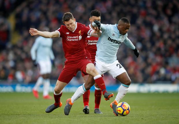 Liverpool's James Milner in action with West Ham United's Patrice Evra.