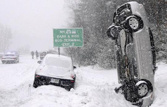 A car landed vertically into a snowbank after a multiple vehicle accident during a snowstorm north of Salem,Massachusetts. No one was injured. Photo: The Eagle-Tribune, Tim Jean/AFP