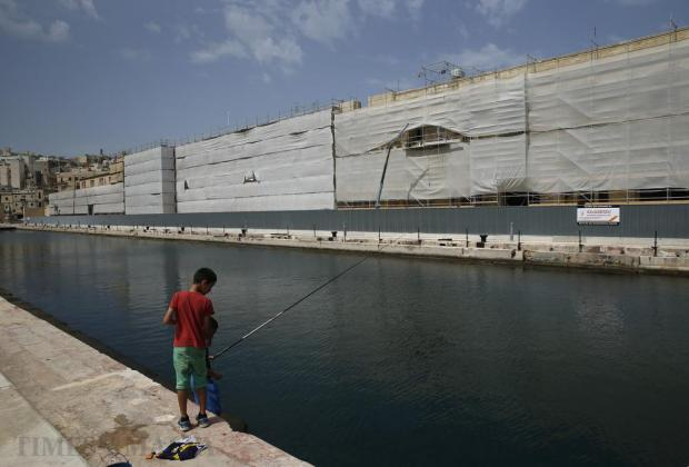 Children try their luck at fishing in Dock One opposite the site where the controversial American University of Malta is being set up in Cospicua on July 2. Photo: Darrin Zammit Lupi