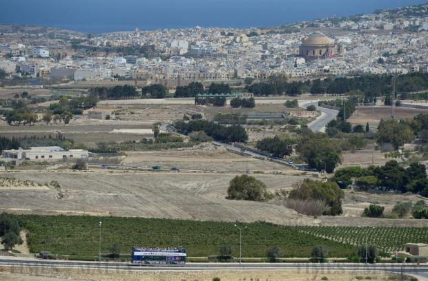 A Malta sightseeing bus passes along a road beneath Mdina on August 16. Photo: Matthew Mirabelli